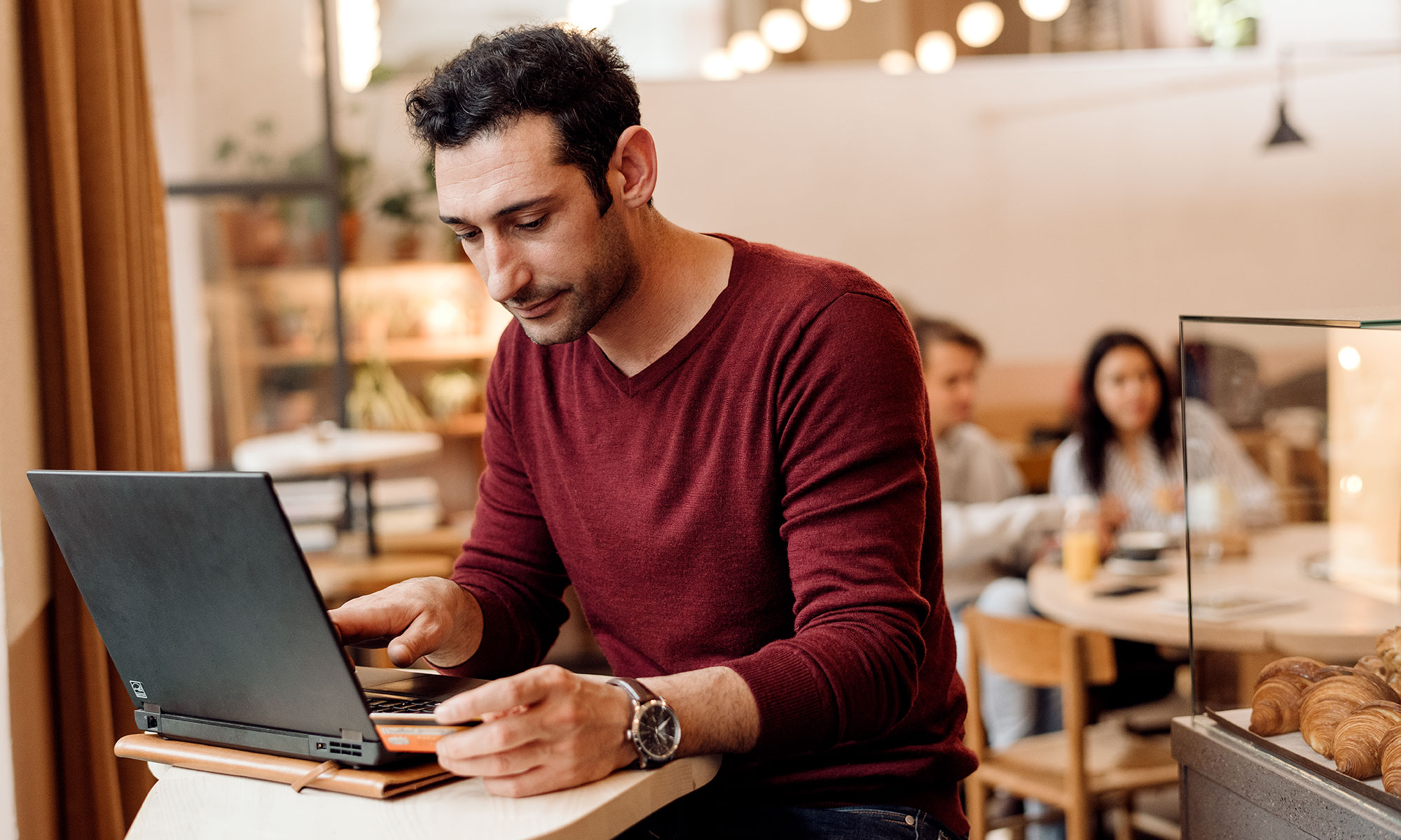 Man working on his laptop in a café.